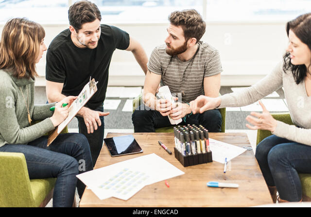 Four people seated at a table, colleagues at a planning meeting holding coloured pens and working on paper and tablets. - Stock Image