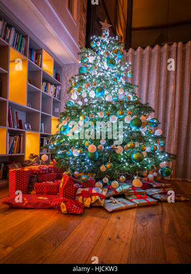 Large Christmas tree with wrapped gifts/presents in home in England UK.Tree has Christmas lights and baubles.Bookshelves - Stock Image