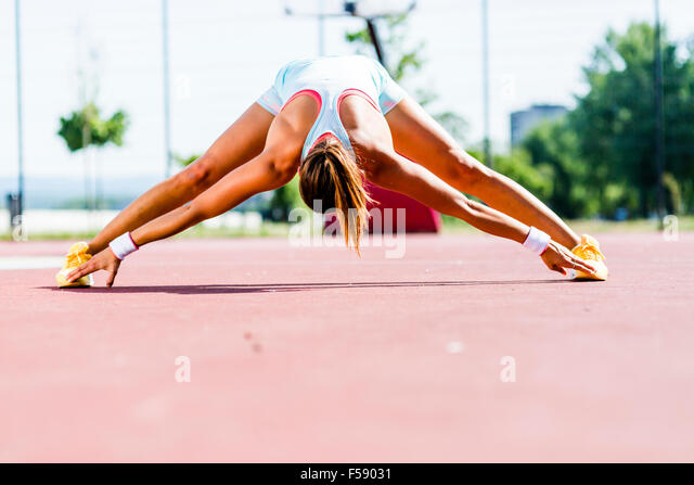 Beautiful young athletic woman stretching in summer before running - Stock-Bilder