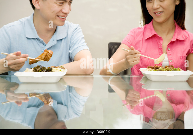 Two office workers having lunch and smiling - Stock Image