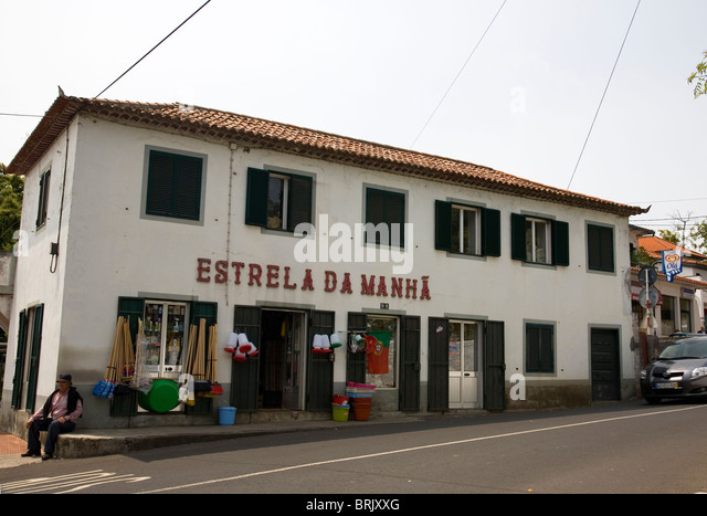Shop in Camacha, madeira - with local sitting on doorstep - Stock Image
