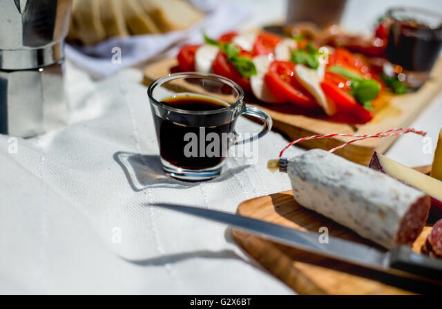 A coffee cup amongst an outdoor picnic of Italian salad and salami - Stock Image