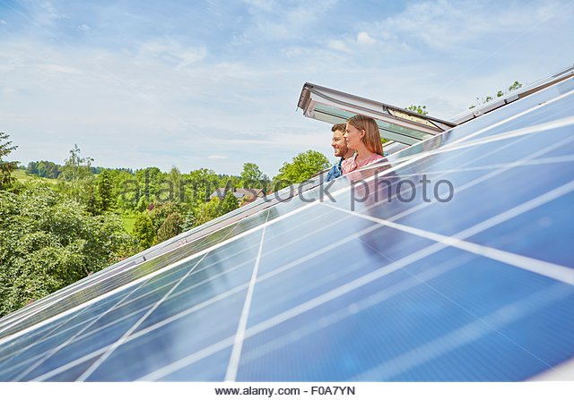 Young couple looking out of window of solar panelled roof - Stock Image