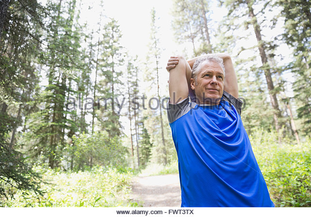 Middle-aged man stretching on outdoors - Stock Image