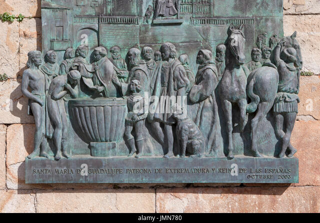 Guadalupe, Spain - February 27, 2017: Plaque depicting the baptism of american Indians brought to Spain from the - Stock Image