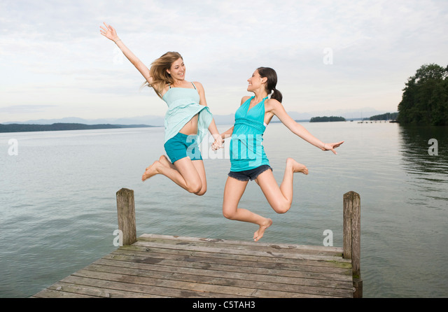 Germany, Bavaria, Starnberger See, Two young women jumping on jetty, laughing, portrait - Stock Image