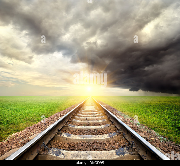 Railroad and clouds in the field at sunrise - Stock Image
