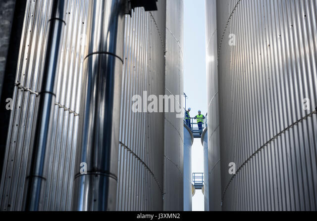 Worker on top of storage tanks in oil blending factory - Stock Image