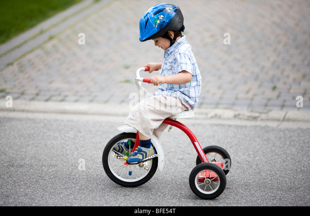 2 1/2 year old boy on a tricycle and wearing a helmet, Montreal, Quebec, Canada - Stock Image
