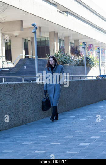 An attractive woman with long dark hair walks past some business premises holding a business case - Stock Image