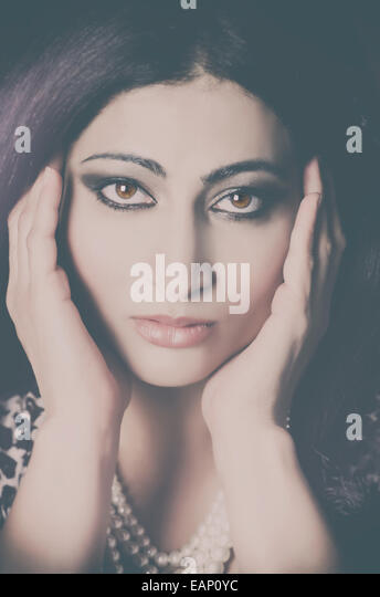 Beautiful Asian woman head in hands - Stock Image