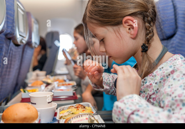 Girl about to eat airline meal - Stock-Bilder
