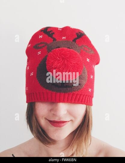 Obscured Face Of Smiling Woman Wearing Red Knit Hat Against Wall - Stock Image