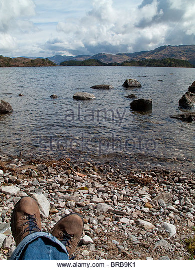 Woman sitting on rocky shore of lake with land in background - Stock Image