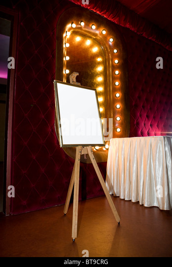 Painter easel with frame and blank canvas in retro room - Stock Image