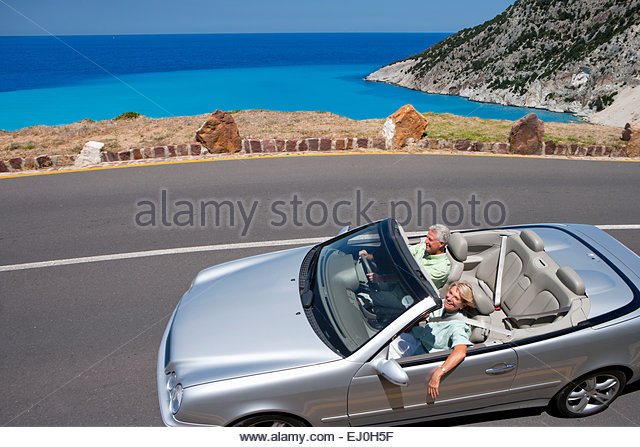 Senior couple driving convertible car along coastal road - Stock Image