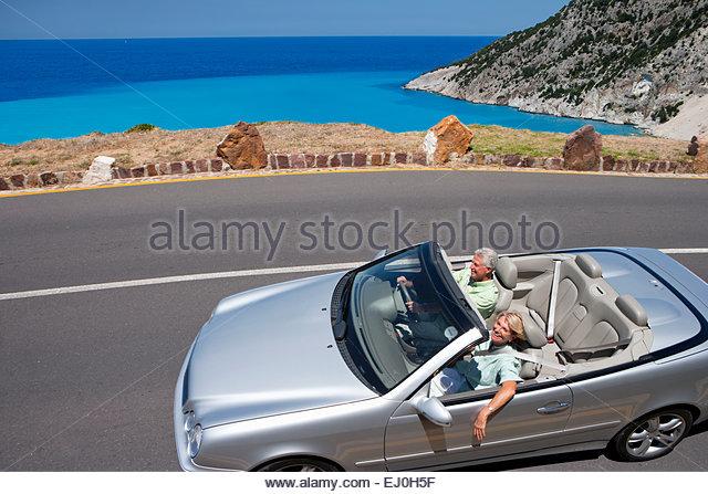 Senior couple driving convertible car along coastal road - Stock Image