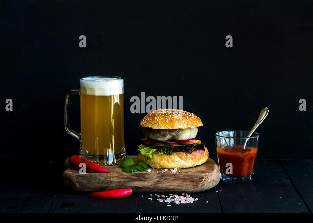 Fresh homemade burger on wooden serving board with spicy tomato sauce, sea salt, herbs and mug of light beer over - Stock Image