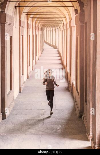Front view of young woman wearing sports clothes jogging - Stock Image
