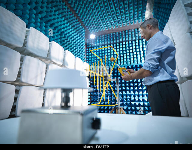 Low angle view of scientist preparing to measure electromagnetic waves in anechoic chamber - Stock-Bilder