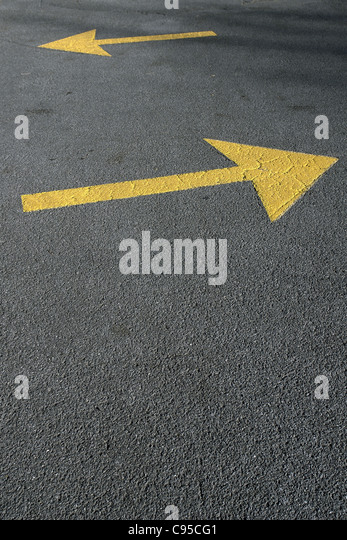 Photograph of Two Yellow Directional Arrows on Road Pavement Copy Space - Stock Image