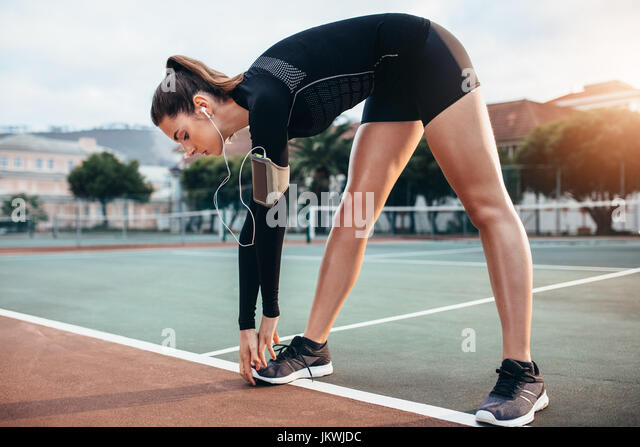 Beautiful young girl doing stretching workout outdoors. Sportswoman doing warmup exercise on tennis court. - Stock Image