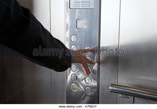 Businessman pushing elevator button close up mid section - Stock Image