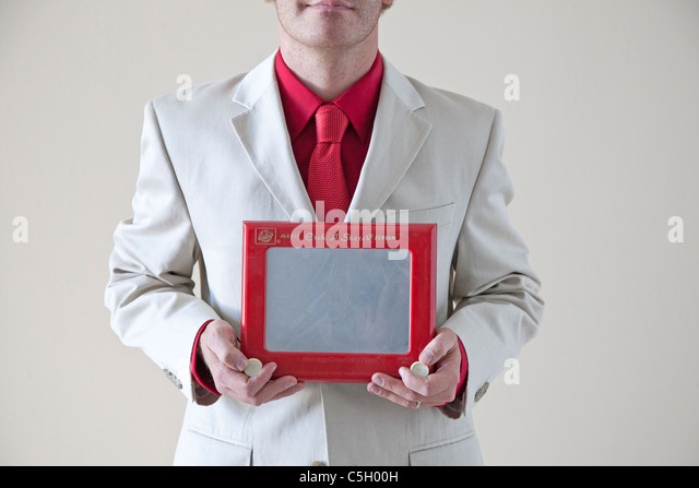 man in suit holds an etch a sketch toy - Stock Image