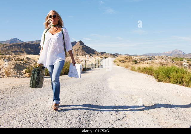 Woman walking alone on dusty road - Stock Image