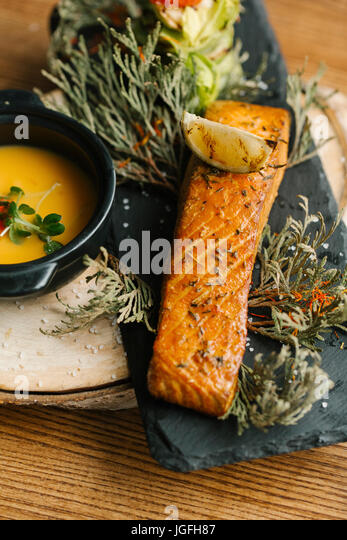 Fish with melted butter and lemon slice - Stock Image