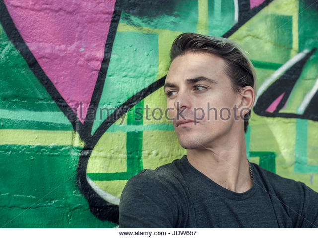 Portrait of young man leaning against graffitied wall - Stock-Bilder