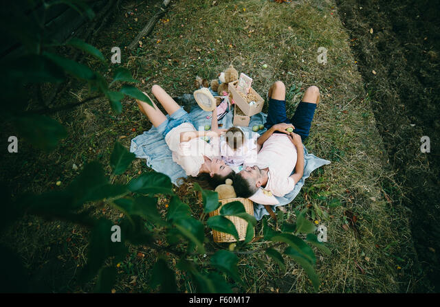 Happy family on lawn in the park - Stock-Bilder