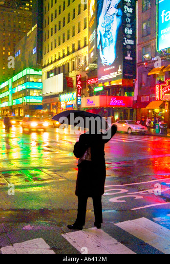 Man Hailing Taxi With Umbrella In The Rain At Night, New York City Times Square, New York, USA - Stock-Bilder