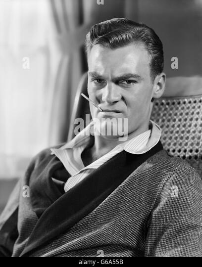 1930s 1940s UNHAPPY MAN SITTING HOLDING THERMOMETER IN MOUTH WEARING ROBE PAJAMAS - Stock Image