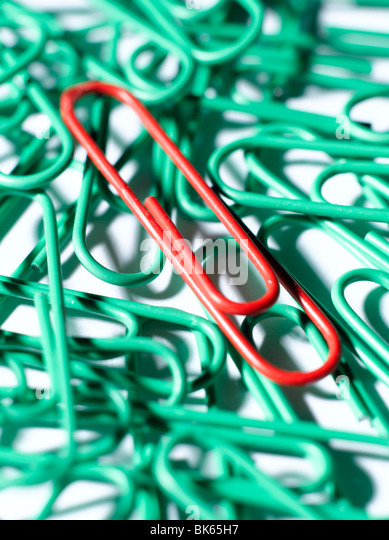 Red paper clip on green - Stock Image