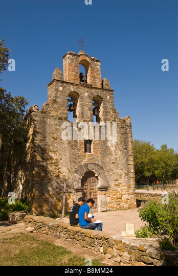 Two college art students drawing in front of Mission Espada, San Antonio Texas tx Missions National Park - Stock Image