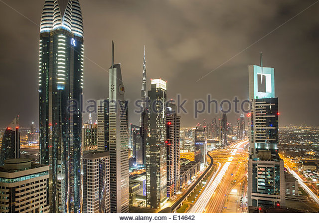 United Arab Emirates, Dubai, Sheikh Zayed Road crosses the financial city center with Burj Khalifa, Night - Stock Image