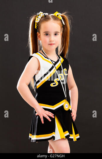 A young Caucasian girl dressed in a Cheer Dance outfit and wearing a medal around her neck. England, UK. - Stock Image