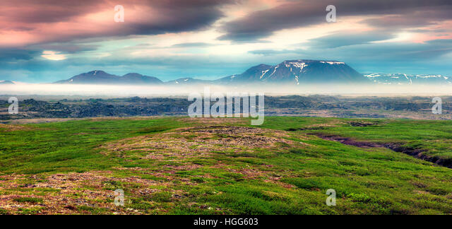 Typical Icelandic landscape with foggy mountains on the horizon. Colorful summer sunrise near the Myvatn lake located, - Stock Image