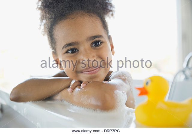 Girl in bubble bath with rubber duck - Stock Image