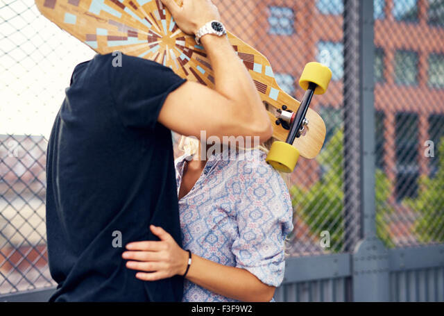 caressing couple hiding behind skateboard and kissing - Stock-Bilder