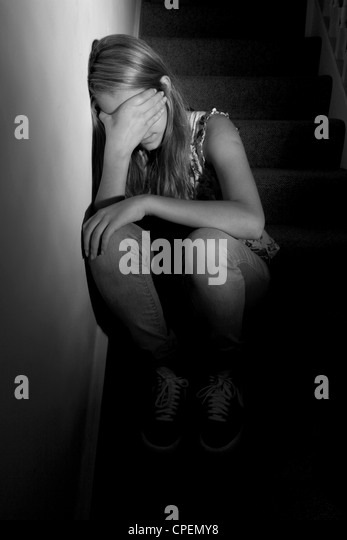 Young girl sitting on dark stairs back view - Stock Image