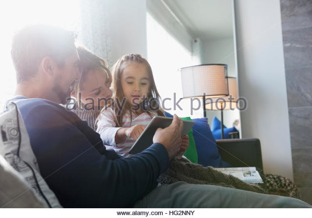 Family using digital tablet on living room sofa - Stock Image