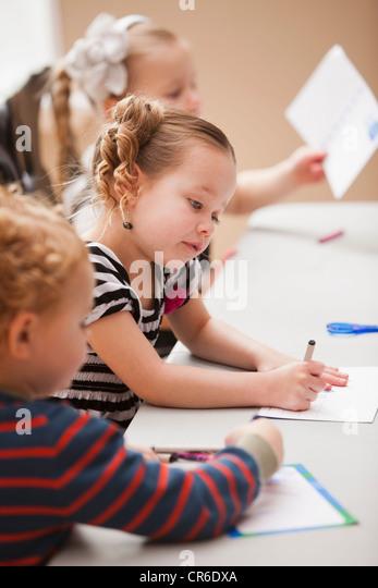 Children (4-5) drawing in kindergarten - Stock Image