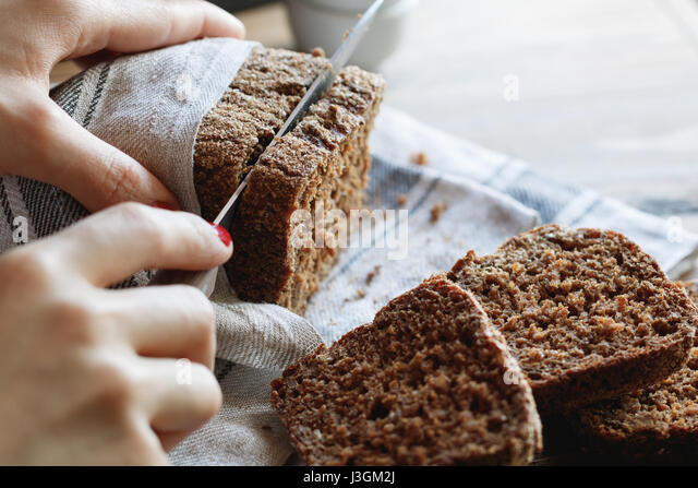 The girl cuts whole-wheat rye bread on a wooden table. - Stock Image