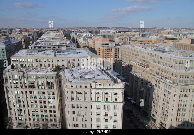 Washington DC Penn Quarter rooftops office buildings view from Old Post Office Pavilion winter snow flag - Stock Image