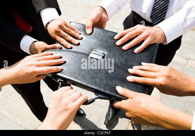 Close-up of people hands holding black leather briefcase simultaneously - Stock Image