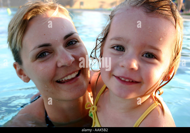 mother and child smiling in swimming pool - Stock Image