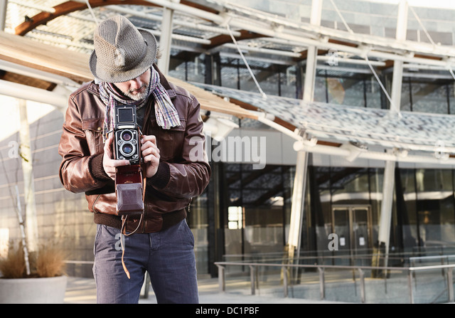 Mid adult man using twin lens reflex camera - Stock Image