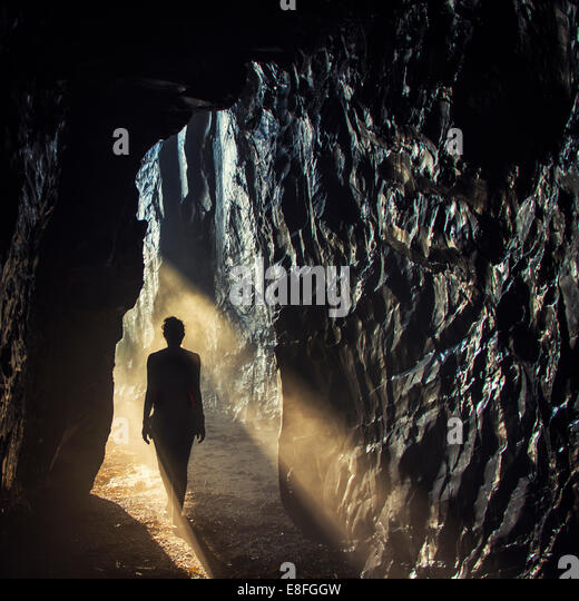 Silhouette of woman standing in sunlight in cave - Stock Image